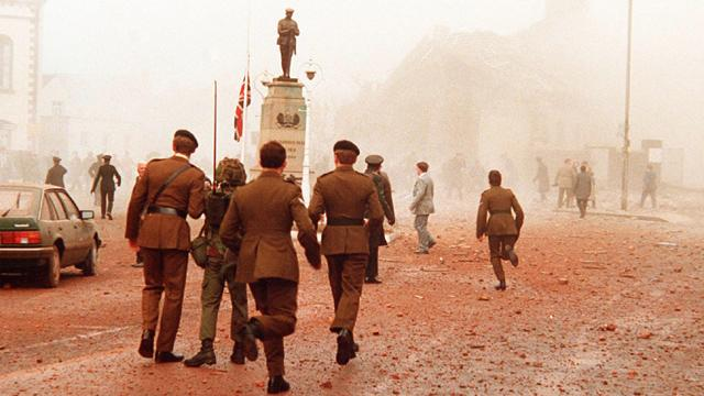 British soldiers rush toward the scene of a bombing in Enniskillen, Northern Ireland, Nov. 8, 1987.