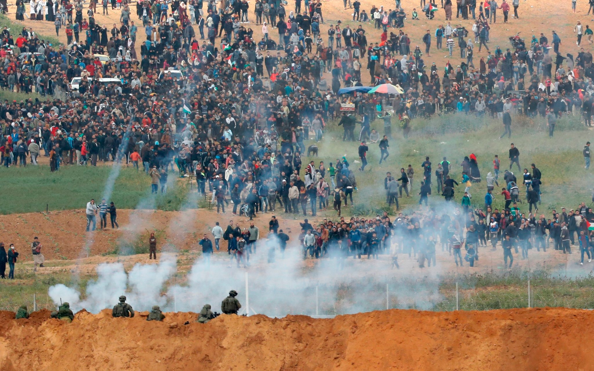 Israeli troops face Palestinian protesters along the Gaza border fence. (Photo: New York Times)